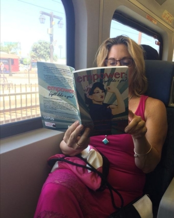 A San Diego Comic-Con commuter reads Empower: Fight Like a Girl on the train to the convention center.  Photo credit: Jeane Wong.